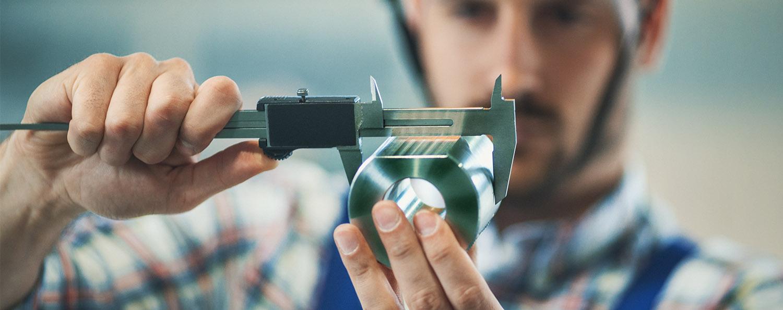 Man measuring fabricated metal part with digital caliper