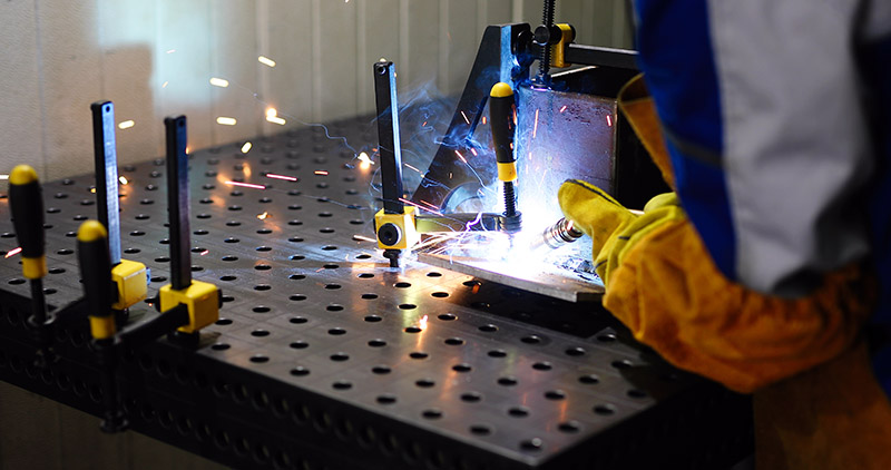 man welds at the factory working in metal industry