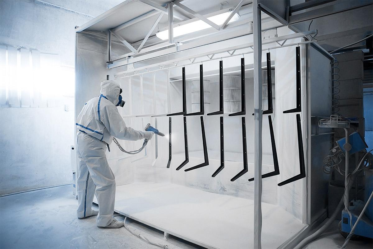 man applying powder coating in spray booth