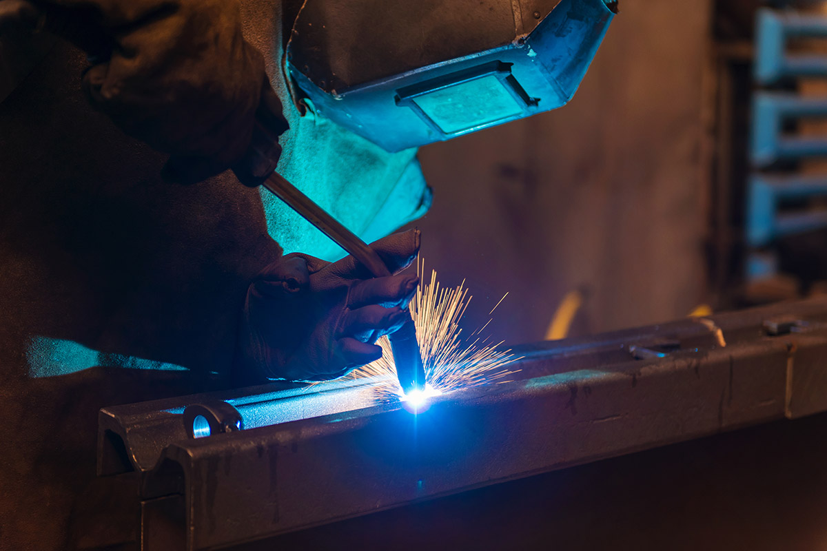 Man welding in metal fabrication shop